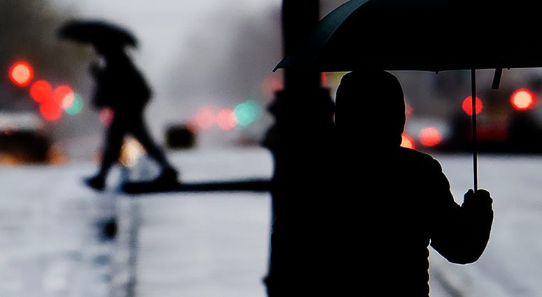 Pedestrians shield from the rain with an umbrellas during a cold rainy day in Center City, Sunday, Dec. 1, 2019 in Philadelphia.