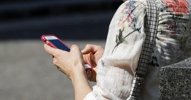 A woman browses her smartphone in Philadelphia in April 8, 2019.