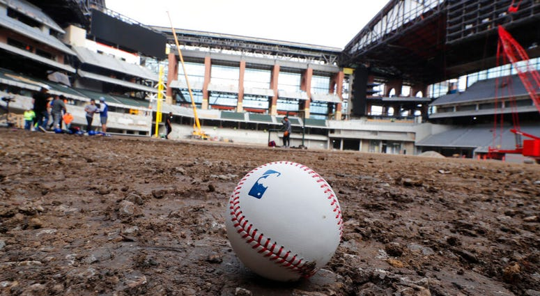 A baseball lies on packed dirt after for a short batting practice during a tour of the under construction baseball field at the new Texas Rangers stadium in Arlington, Texas.