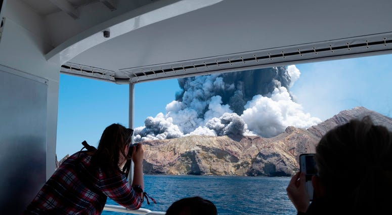 Tourists on a boat look at the eruption of the volcano on White Island, New Zealand, on Dec. 9, 2019.