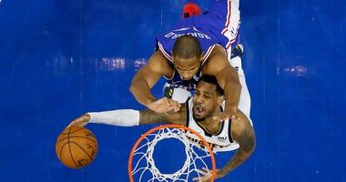 Denver Nuggets' Monte Morris, bottom, goes up for a shot against Philadelphia 76ers' Al Horford during the second half of an NBA basketball game, Tuesday, Dec. 10, 2019, in Philadelphia.