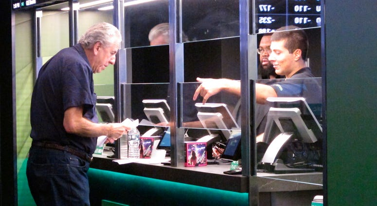 In this Oct. 8, 2019 photo, a man makes a sports bet at Resorts casino in Atlantic City, N.J. In November 2019, New Jersey's casinos and racetracks took in nearly $563 million worth of sports bets, a new monthly record.