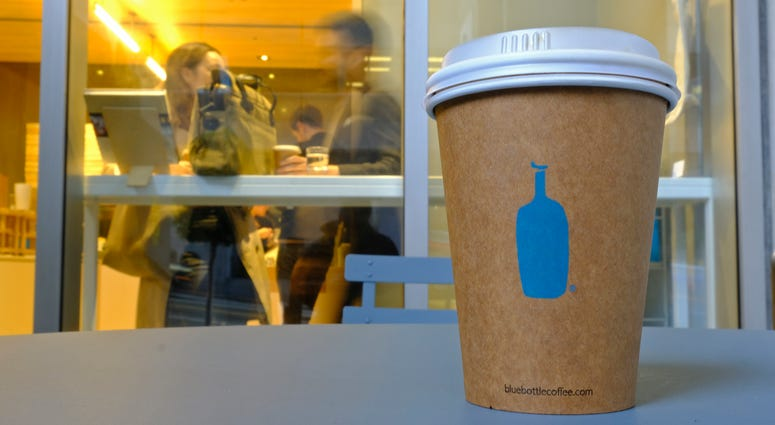 A Blue Bottle Coffee paper to-go cup rests on a table outside one of their cafes in San Francisco.