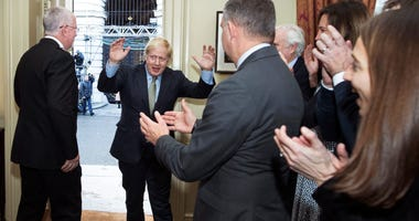 Britain's Prime Minister Boris Johnson is greeted by staff as he returns to 10 Downing Street, London, after meeting Queen Elizabeth II at Buckingham Palace and accepting her invitation to form a new government, Friday Dec. 13, 2019.