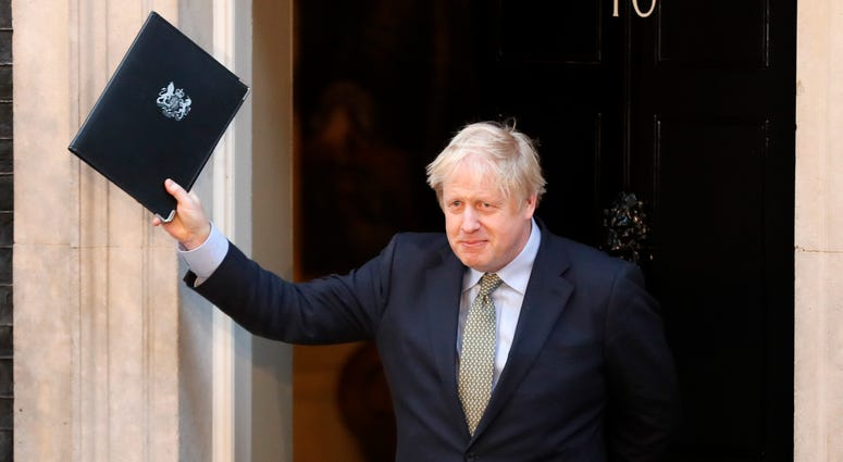 Britain's Prime Minister Boris Johnson waves after addressing the media outside 10 Downing Street in London Friday.