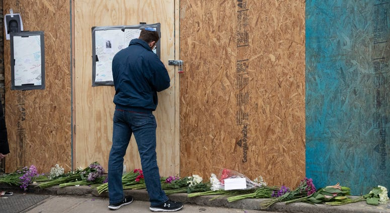 Alex Seligson pens a note of condolence Friday, Dec. 13, 2019 in Jersey City, N.J. at the boarded up kosher grocery store where three people and two gunmen were killed on Tuesday.