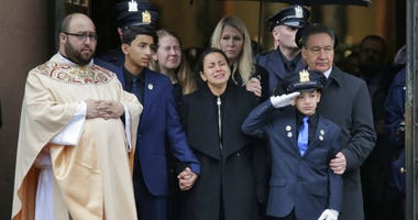 Mourners of Jersey City Police Detective Joseph Seals, including his wife Laura Seals, center, watch as his casket is carried out of the church.
