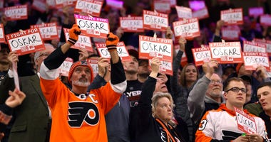 Fans hold signs in support of Philadelphia Flyers' Oskar Lindblom during a stoppage in the first period of an NHL hockey game against the Anaheim Ducks, Tuesday, Dec. 17, 2019, in Philadelphia.