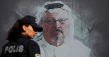 A Turkish police officer walks past a picture of slain Saudi journalist Jamal Khashoggi prior to a ceremony, near the Saudi Arabia consulate in Istanbul, marking the one-year anniversary of his death.