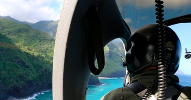 A Coast Guard search and rescue team looks over Napali Coast State Wilderness Park for a tour helicopter that disappeared in Hawaii with seven people aboard on Friday.