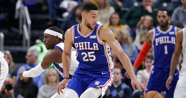Philadelphia 76ers' Ben Simmons (25) makes a move against Indiana Pacers' Aaron Holiday (3) during the first half of an NBA basketball game.