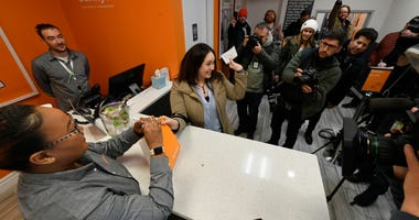 Jackie Ryan of Forest Park, Ill., becomes the first person in Illinois to purchase recreational marijuana as she purchases marijuana products from employee Brea Mooney left, at Sunnyside dispensary Wednesday, Jan. 1, 2020, in Chicago.