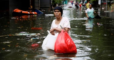 A woman wades through flood water in Jakarta, Indonesia, Saturday.