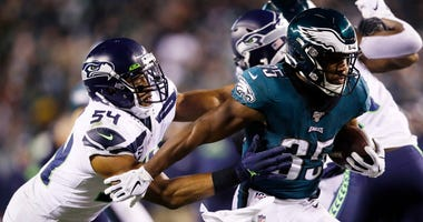 Philadelphia Eagles' Boston Scott (35) tries to rush past Seattle Seahawks' Bobby Wagner (54) during the second half of an NFL wild-card playoff football game, Sunday, Jan. 5, 2020, in Philadelphia.