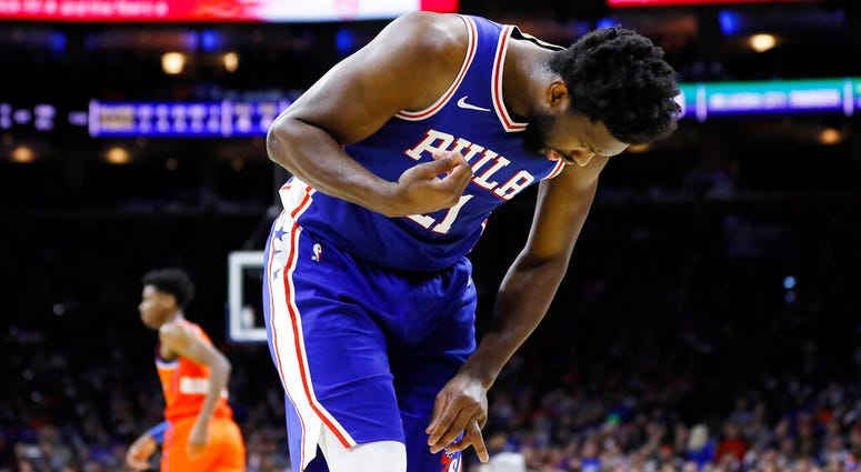 Philadelphia 76ers' Joel Embiid looks at his injured finger during the first half of an NBA basketball game against the Oklahoma City Thunder.