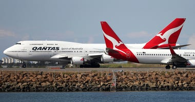Two Qantas planes taxi on the runway at Sydney Airport in Sydney, Australia, in 2015.