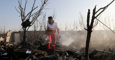 A rescue worker searches the scene where an Ukrainian plane crashed in Shahedshahr, southwest of the capital Tehran, Iran, Wednesday, Jan. 8, 2020.