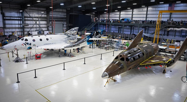 Virgin Galactic's next passenger spaceship, at right, stands on its landing gear in what is known as a weight-on-wheels test.