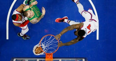 Philadelphia 76ers' Norvel Pelle, right, dunks the ball as Tobias Harris, left, and Boston Celtics' Daniel Theis look on during the second half of an NBA basketball game, Thursday, Jan. 9, 2020, in Philadelphia.