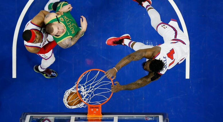 Philadelphia 76ers' Norvel Pelle, right, dunks the ball as Tobias Harris, left, and Boston Celtics' Daniel Theis look on during the second half of an NBA basketball game, Thursday, Jan. 9, 2020, in Philadelphia.