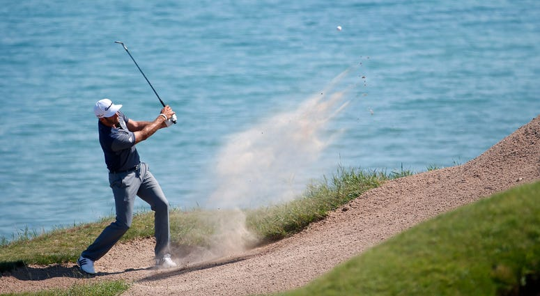 Dustin Johnson hits from a bunker on the third hole during the third round of the PGA Championship golf tournament at Whistling Straits in Haven, Wis.