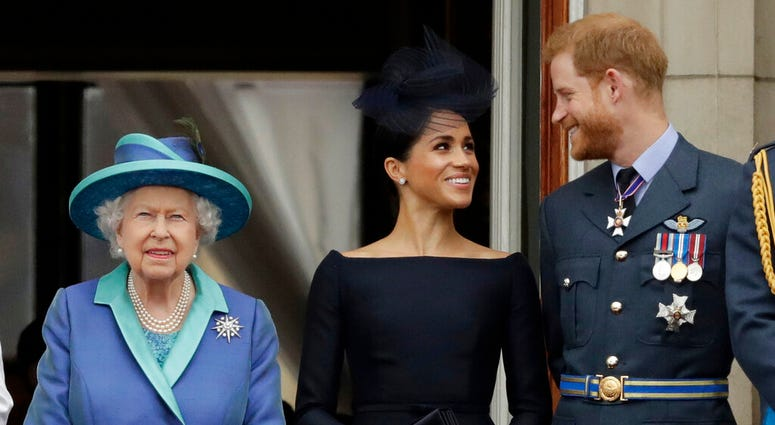 In this Tuesday, July 10, 2018 file photo Britain's Queen Elizabeth II, and Meghan the Duchess of Sussex and Prince Harry watch a flypast of Royal Air Force aircraft pass over Buckingham Palace in London.