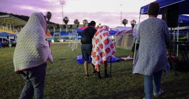 People get up after spending the night in a baseball stadium amid aftershocks and without electricity after the 6.4 magnitude earthquake in Guayanilla, Puerto Rico, at sunrise Friday.