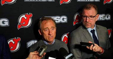 New Jersey Devils owner Josh Harris, left, announces interim general manager Tom Fitzgerald, right, to replace Ray Shero prior to an NHL hockey game Sunday, Jan. 12, 2020, in Newark, N.J.