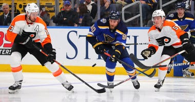 Philadelphia Flyers center Kevin Hayes (13) and center Philippe Myers (5) defend against St. Louis Blues center Ryan O'Reilly (90) during the second period of an NHL hockey game Wednesday, Jan. 15, 2020 in St. Louis.