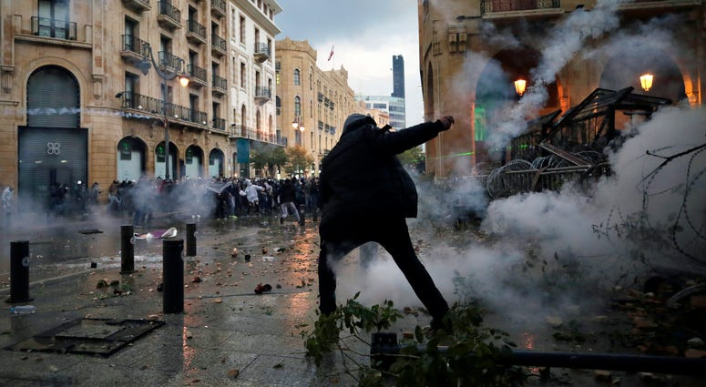 Anti-government protesters clash with the riot police, during a protest at a road leading to the parliament building in Beirut, Lebanon, Saturday.