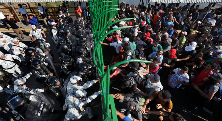 Migrants charge on the Mexican National Guardsmen at the border crossing between Guatemala and Mexico in Tecun Uman, Guatemala, Saturday.