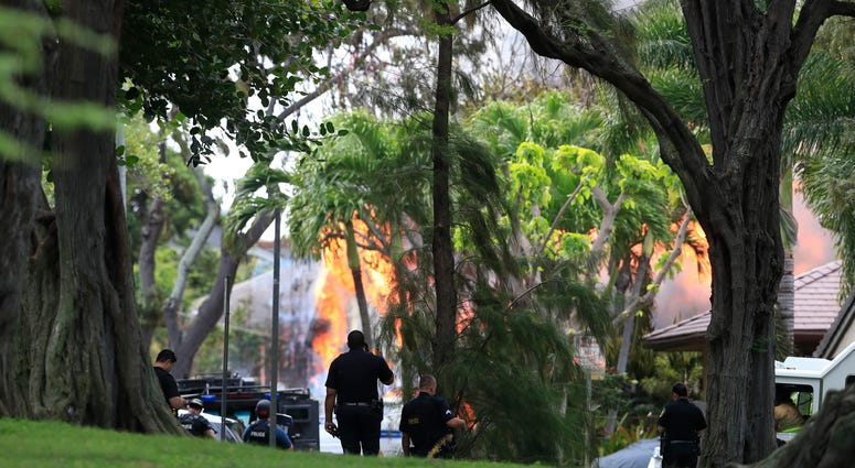 Honolulu police watch a house fire after a shooting and domestic incident at a residence on Hibiscus Road near Diamond Head on Sunday, Jan. 19, 2020, in Honolulu.