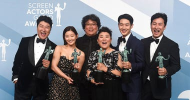 "Kang-Ho Song, from left, Park So-dam, Bong Joon-ho, Jang Hye-jin, Choi Woo-shik, and Lee Sun Gyun pose in the press room with the award for outstanding performance by a cast in a motion picture for ""Parasite."""