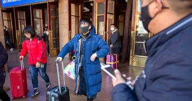 Travelers wear face masks as they walk outside of the Beijing Railway Station in Beijing, Monday, Jan. 20, 2020.