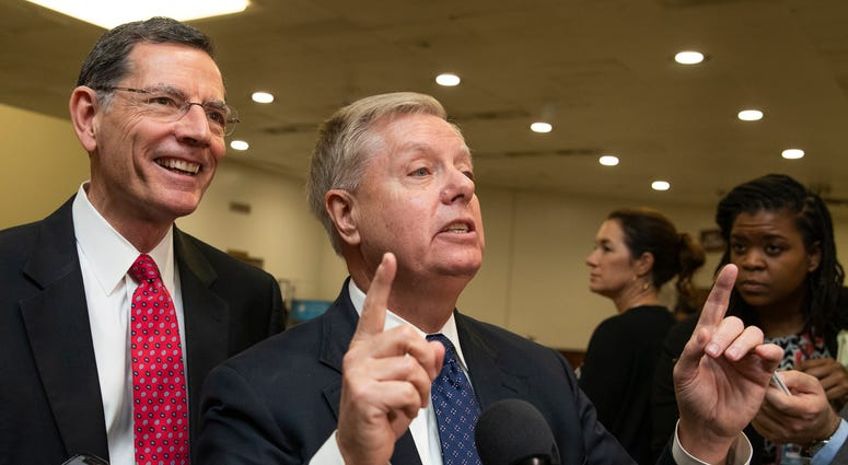 Sen. Lindsey Graham, R-S.C., with Sen. John Barrasso, R-Wyo., speaks to reporters on Capitol Hill in Washington, Saturday, Jan. 25, 2020.