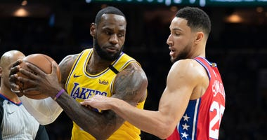 Los Angeles Lakers' LeBron James, left, tries to make his move on Philadelphia 76ers' Ben Simmons, right, during the first half of an NBA basketball game, Saturday, Jan. 25, 2020, in Philadelphia.