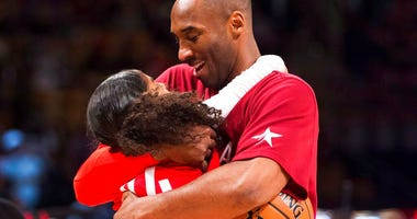 Los Angeles Lakers Kobe Bryant (24) hugs his daughter Gianna on the court in warm-ups before first half NBA All-Star Game basketball action in Toronto.