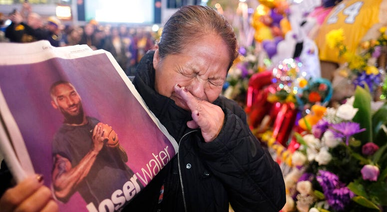 Ana Sebastian, from Guatemala, shows a copy of newspaper with a picture of the late Kobe Bryant at a memorial for Bryant near Staples Center, Monday, Jan. 27, 2020, in Los Angeles.