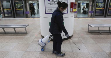 An employee disinfects the platform in hopes to prevent transmission of the coronavirus at a subway station in Seoul, South Korea, Tuesday, Jan. 28, 2020.
