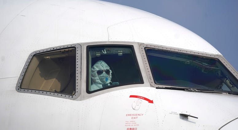 A pilot wearing a protective suit parks a cargo plane at Wuhan Tianhe International Airport in Wuhan in central China's Hubei Province, Tuesday, Jan. 28, 2020.