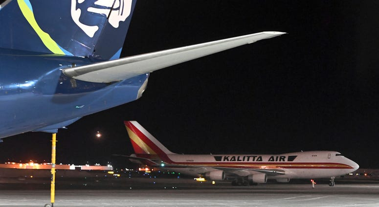 An airplane, background, carrying U.S. citizens being evacuated from Wuhan, China, makes a refueling stop at the north terminal at Ted Stevens Anchorage International Airport in Anchorage, Alaska Tuesday evening, Jan. 28, 2020.