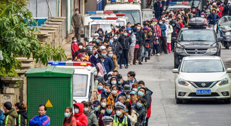 In this Jan. 29, 2020 photo, people line up to buy face masks from a medical supply company in Nanning in southern China's Guangxi Zhuang Autonomous Region.