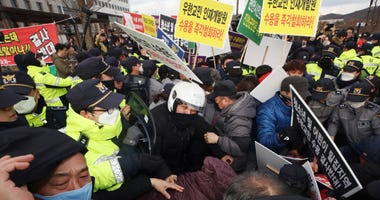 Residents scuffle with police officers during a rally to protest the government's decision to quarantine South Koreans returning from Wuhan in their home town in Jincheon, South Korea, Thursday, Jan. 30, 2020.