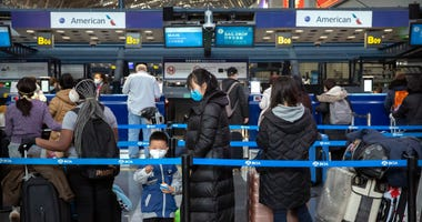 Travelers wearing face masks line up to check in for an American Airlines flight.