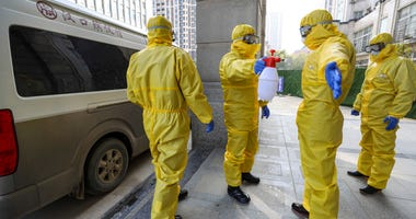 Funeral workers disinfect themselves after handling a coronavirus victim.