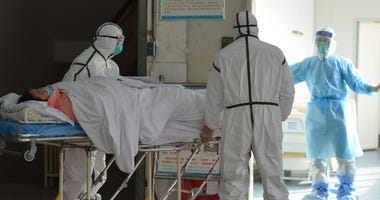 Medical workers in protective suits move a coronavirus patient into an isolation ward at the Second People's Hospital in Fuyang in central China's Anhui Province, Saturday, Feb. 1, 2020.