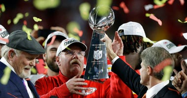 Kansas City Chiefs chairman Clark Hunt, right, hands the trophy to head coach Andy Reid after the chiefs defeated the San Francisco 49ers in the NFL Super Bowl 54 football game.