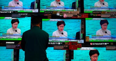 A man wears protective face masks stands in front of TV screens broadcasting Hong Kong Chief Executive Carrie Lam delivering a speech in Hong Kong, Monday, Feb. 3, 2020.