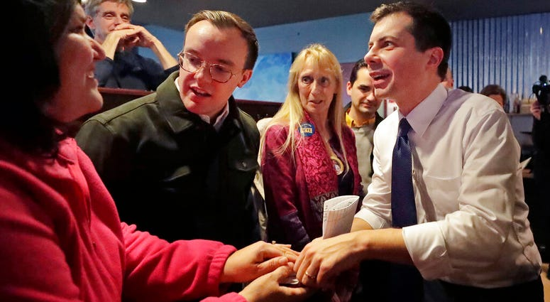 Democratic presidential candidate former South Bend Mayor Pete Buttigieg, right, and his husband, Chasten Buttigieg, left, greet people at a campaign event, Tuesday, Feb. 4, 2020, in Hampton, N.H.