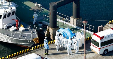 Medical workers in protective suits lead a passenger tested positive for a new coronavirus from the cruise ship Diamond Princess at Yokohama Port in Yokohama, south of Tokyo, Wednesday, Feb. 5, 2020.
